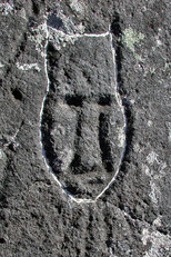 "Petroglyph of an elongated figure with a prominent forehead ending in narrow points along each side of the face; the base of the figure is oval in shape. The carvings beneath the chin may symbolize shamanic breathwork. The whitened edges indicate relatively recent ""updating"" work on the carving, 2004"
